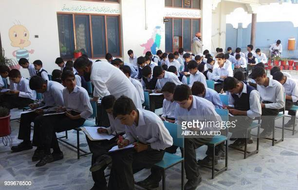 Students sit for a final exam at the former school of Pakistani activist and Nobel peace laureate Malala Yousafzai at her hometown in Mingora the...