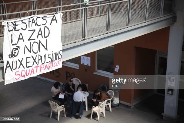 Students sit in a yard under a banner reading 'University and ZAD no evictions squat everywhere' in a building occupied by students at SaintDenis...
