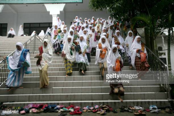 Students sit in circles as they read the holy book of Quran during the first day of the holy fasting month of Ramadan at ArRaudlatul Hasanah Islamic...