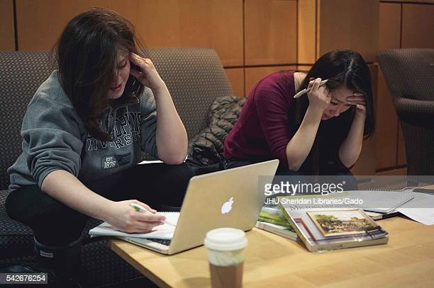 Students sit on a couch, studying intently in the Milton S. Eisenhower Library on the Homewood campus of the Johns Hopkins University. 2014. Courtesy...