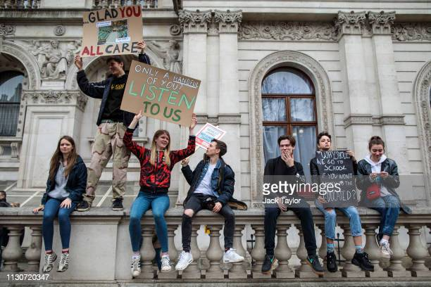 Students sit on a wall with signs as schoolchildren take part in a student climate protest on March 15 2019 in London England Thousands of pupils...