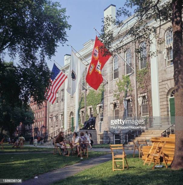Students sit on chairs in front of the statue of John Harvard in the Harvard Yard area of the Harvard University campus in Cambridge, Massachusetts,...