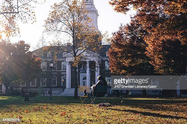 Students sit on lounge chairs studying in front of Gilman Hall on the leavecovered Keyser quadrangle on the Homewood campus of the Johns Hopkins...