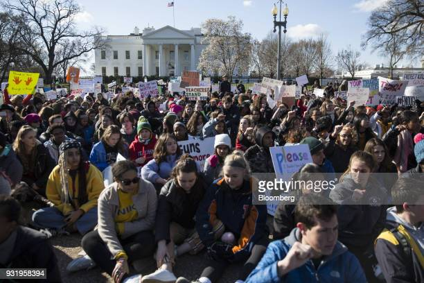 Students sit outside the White House during the ENOUGH National School Walkout rally in Washington DC US on Wednesday March 14 2018 Politicians law...