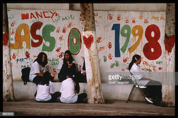 Students sit under a banner at the Ahliyyah School for Girls May 17 1998 in Amman Jordan Still a teenager when crowned in 1952 King Hussein has led...