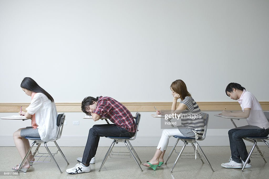 Students Sitting At Desk Side View Stock Photo