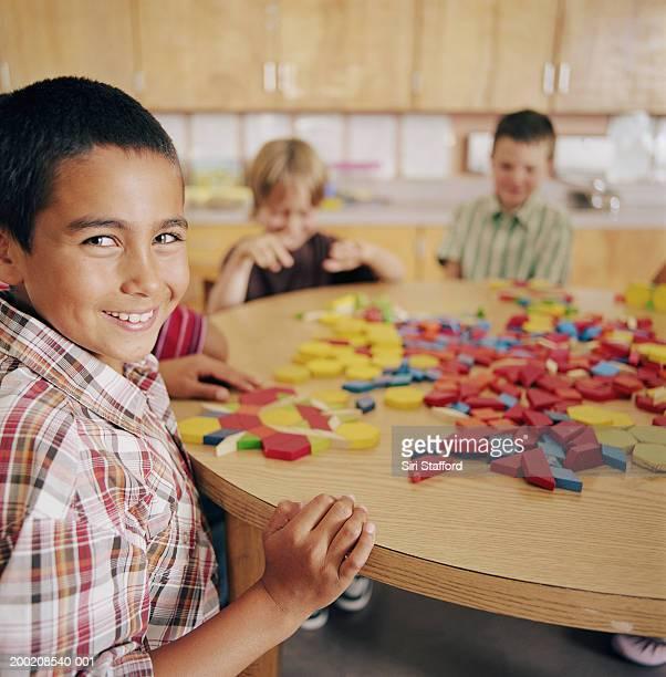 studenten (5-10) sitzen am tisch im klassenzimmer, porträt - schulkind nur jungen stock-fotos und bilder