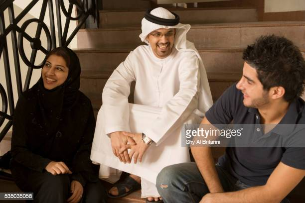 students sitting by the stairs and enjoying a chat - gulf countries stock pictures, royalty-free photos & images