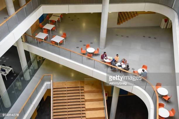 étudiants assis sur une surface surélevée au collège moderne - mezzanine photos et images de collection