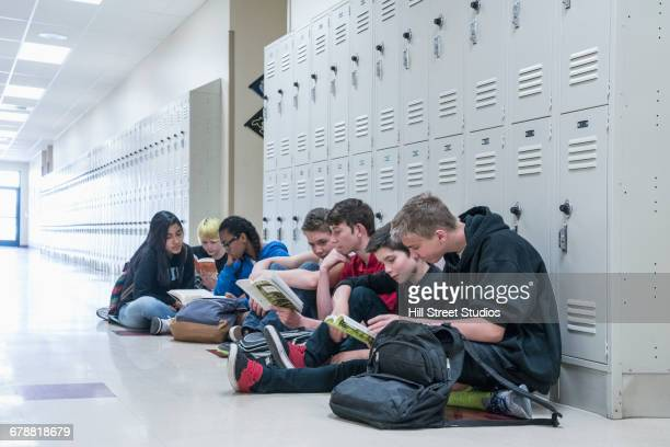 students sitting on floor of school corridor reading books - locker stock pictures, royalty-free photos & images