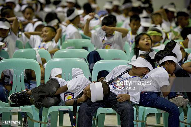 Students sleep on chairs as they wait hours prior to the departure of Pope Francis at Villamor Airbase in Manila on January 19 2015 Pope Francis flew...