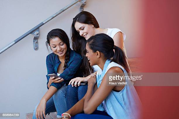 students smiling and looking at phone - looking down her blouse stock photos and pictures