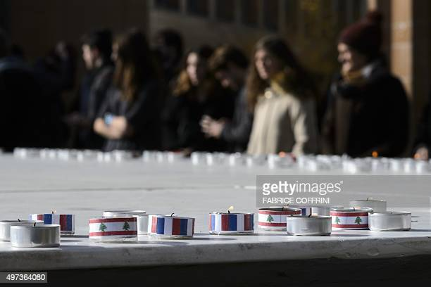 Students stand behind candles with colours of French and Lebanese national flags during a gathering on November 16, 2015 at the Swiss Federal...