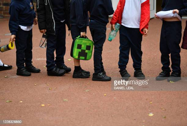 Students stand in line as they wait to enter their classrooms on their their first day of school after the summer break, at St Luke's Church of...