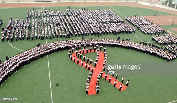Students stand in the shape of a red ribbon in an activity to mark World Aids Day November 30 2007 in Chengdu China