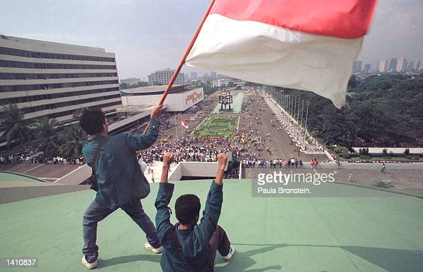 Students stand on the roof of the parliament building waving the Indonesian flag as they demand the resignation of president Suharto May 20 1998 in...