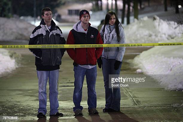 Students stand outside the crime scene near Cole Hall following a shooting on the Northern Illinois University campus February 14 2008 in De Kalb...