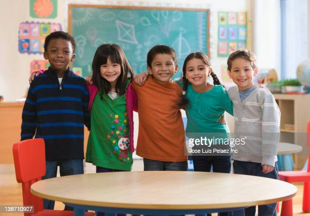 students standing together in classroom - multiculturalism stock pictures, royalty-free photos & images