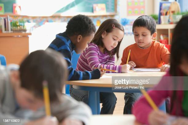 students studying in classroom - elementary school stock pictures, royalty-free photos & images