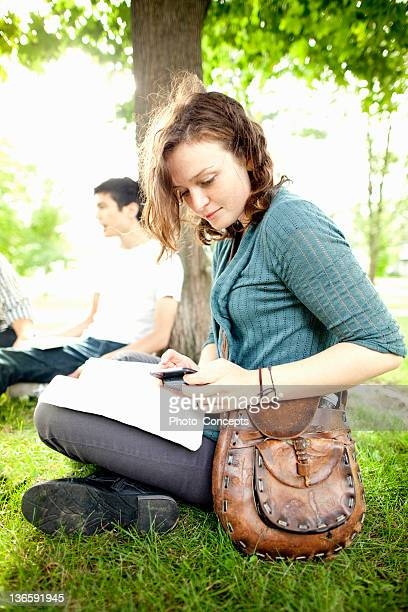 Students studying in grass at park
