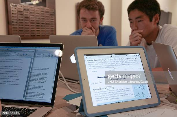 Students studying on the second level M Level of the Milton S Eisenhower library at Johns Hopkins University surrounded by laptops iPads and study...