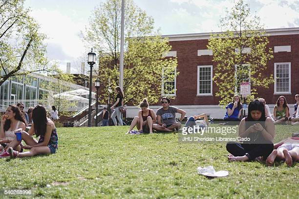 Students sunbathe in groups on the grassy Beach in front of Milton S Eisenhower Library during Spring Fair a studentrun spring carnival at Johns...