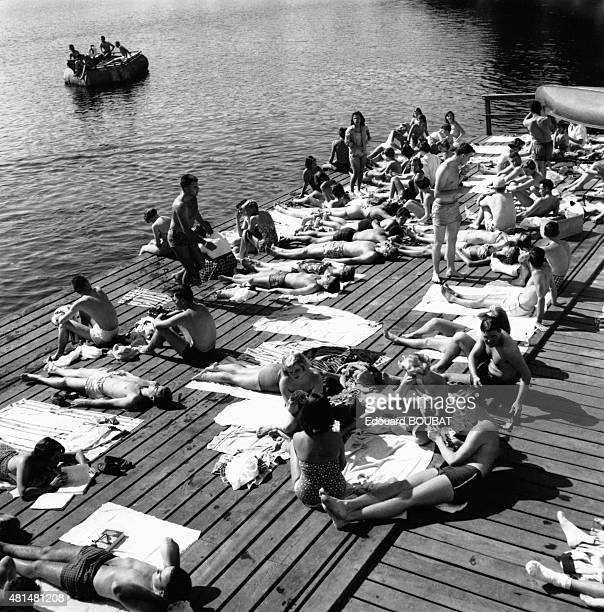 Students sunbathing at a lake on the campus of Stanford University in Palo Alto United States