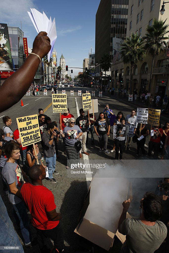 Students symbolically 'burn' their student loan bills and mock bills by throwing them into a box with a smoke machine during a demonstration on Hollywood Boulevard to protest the rising costs of student loans for higher education on September 22, 2012 in the Hollywood section of Los Angeles, California. Citing bank bailouts, the protesters called for student debt cancelations.