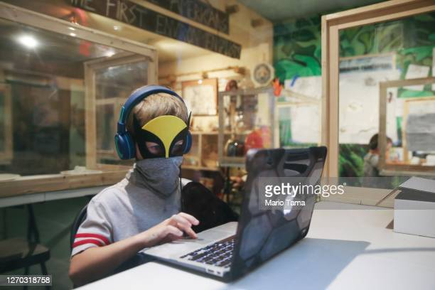 Students take livestream classes while seated in socially distanced protective learning pods at STAR Eco Station Tutoring & Enrichment Center on...