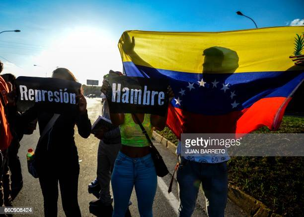 Students take part in a protest against Venezuelan President Nicola Maduro on the main highway in Caracas on March 30 2017 Venezuela's Supreme Court...