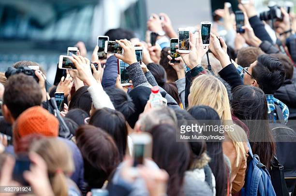 Students take photographs using their mobile phones as Queen Elizabeth II opens the School of Veterinary Medicine at the University of Surrey on...