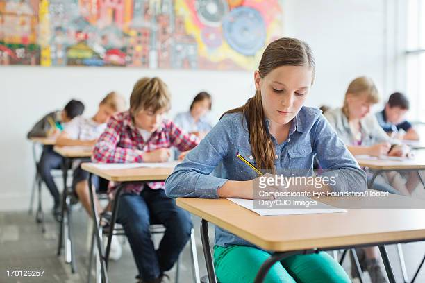 students taking a test in classroom - schoolkinderen stockfoto's en -beelden