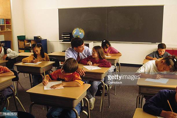 students taking test as teacher assists a student - 20th century stock pictures, royalty-free photos & images