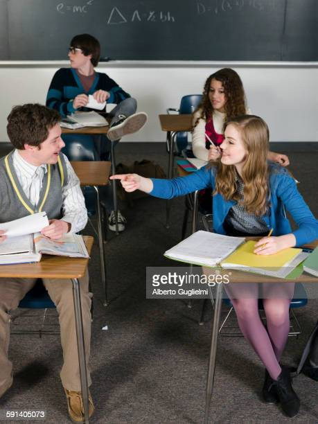 Students talking at desks in classroom