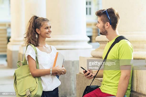 Estudiantes hablando frente a escuela