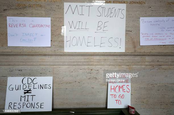 Students tape signs to a wall on campus during an MIT international student demonstration on March 12 2020 in Cambridge MA Students at the...