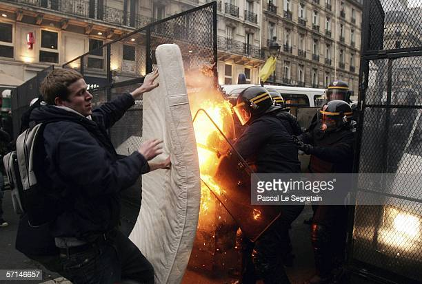 Students throw a burning mattress on riot Police officers during a protest against Youth Employment Contract on March 21 2006 in Paris France Unions...