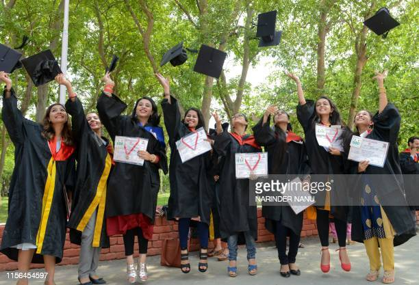 Students throw caps in the air after receiving their Bachelor of Art degree during the Golden Jubilee Year Convocation at the Guru Nanak Dev...