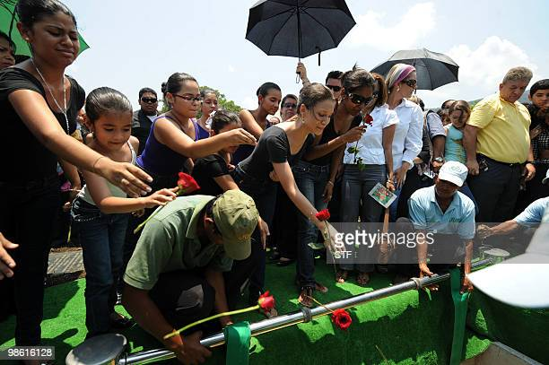 Students throw flowers into the grave during the burial of television journalist and university professor Jorge Alberto Orellana in San Pedro Sula...