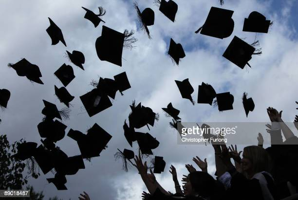 Students throw their mortarboards in the air during their graduation photograph at the University of Birmingham degree congregations on July 14, 2009...