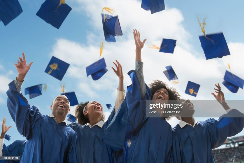 Students throwing caps at graduation : Stock Photo