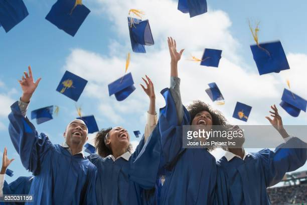 students throwing caps at graduation - graduation cap stock pictures, royalty-free photos & images