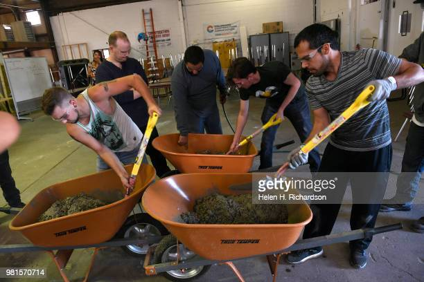 Students Tim Constant left and Muhammad Sarwari right learn how blend concrete in a wheelbarrow during a class in concrete finishing that is part of...