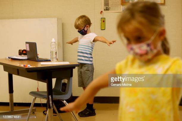 Students Tristen Wild, left, and Maya Haldeman participate in a Zoom lesson from a class overseen by teachers with the YMCA at the Anza Elementary...