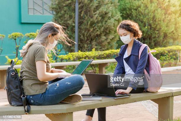 students trying to access the internet in front of campus - campus stock pictures, royalty-free photos & images