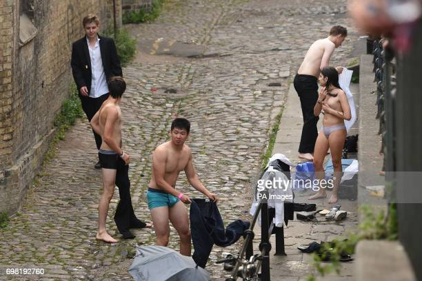 NUDITY** Students undress before swimming in the River Cam after celebrating the end of the academic year at one of the Cambridge University May Balls