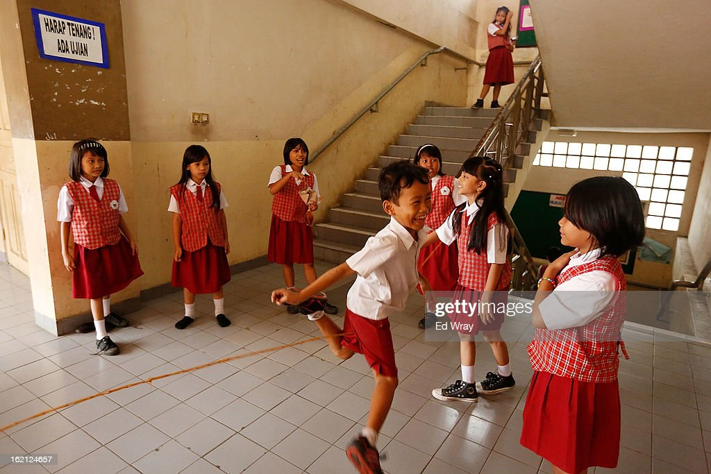 Students use a rope made from rubber bands to play jump rope between classes at their school on February 19, 2013 in Jakarta, Indonesia. A new schools curriculum to take effect in July, 2013 has drawn criticism for its plans to drop science and english classes to provide more time for social and religious education, at a time when Indonesian students are falling behind other countries in the region in Science and Math.