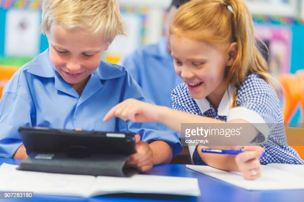 students using a digital tablet in a classroom. - uniform stock pictures, royalty-free photos & images