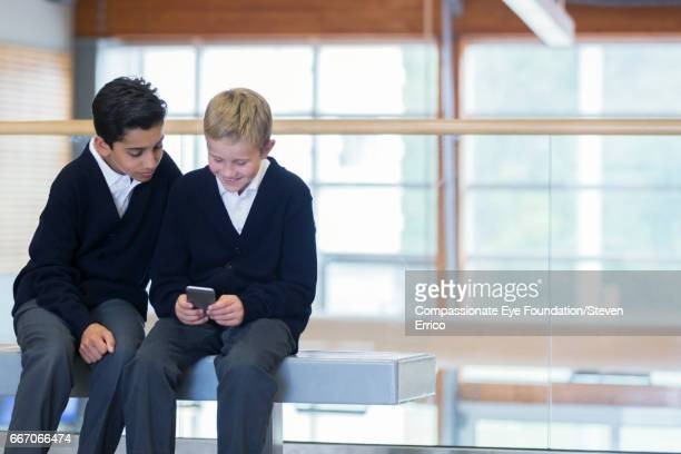 Students using cell phone in hallway