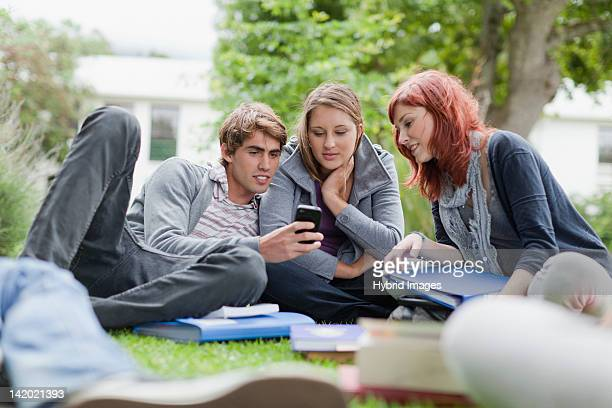 Students using cell phone on grass